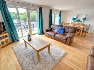 Contemporary styling in this lovely spacious living room with wood floors, leather suite and double patio doors