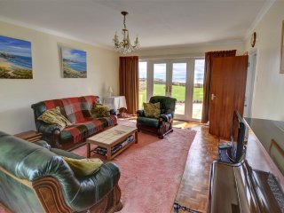 The well-furnished sitting room, with piano, has patio doors at both ends, allowing lots of light and easy access to the garden