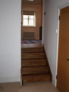 A short flight of wooden stairs from the kitchen dining room to the upper ground floor hallway