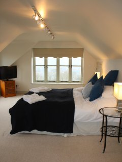 On the first floor, the master double bedroom, complete with TV, bath shower ensuite & those views.