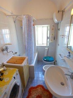Bagno con vasca, doccia, vista mare, asciugamani e lavatrice
