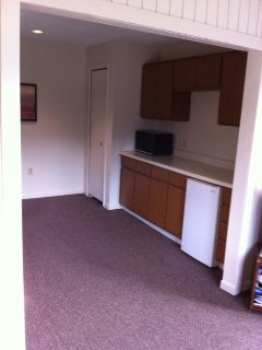 Closet with hanging shelves for clothes. Cabinets with items for use. Mini-frig.