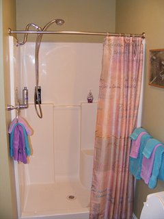Large sit down shower with extended hand wand.