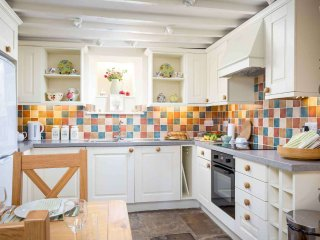 The well presented kitchen includes a dining table with seating for four
