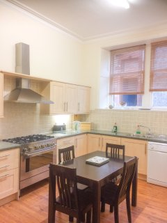 Big full fitted kitchen with seating and rear door to small private enclosed outdoor area