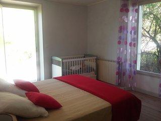 chambre avec 1 lit de 160 et lit bébé à barreaux