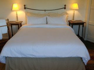 Main bedroom with kingsize bed, wardrobe, chest of drawers. White cotton bedlinen provided.