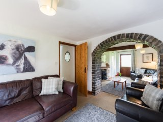 Ashley Cottage's living room, with comfortable leather sofas and media centre.