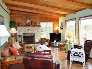 Living room with a flat screen satellite TV/VCR/Blu-Ray DVD with sound bar, wood burning fireplace, leather couch, three arm chairs, recliner, a baby grand piano and large picture windows providing beautiful ocean views.