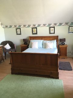 Large bedroom with large wooden framed bed, with views over pool and garden.