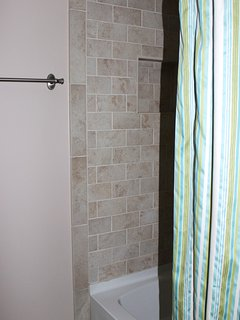 The updated bathroom has a tiled shower/tub.