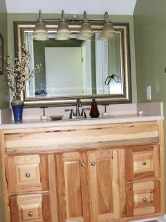 The hall bath is between the two bedrooms & has an updated cabinet with granite.