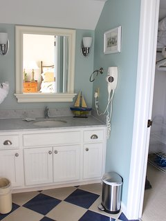 In the master bathroom, the sink is separate from the shower area.