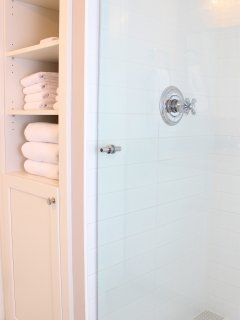 The roomy shower has floor to ceiling glass and great tile.