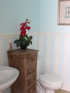 Off the living room is a powder room with a pedestal sink.