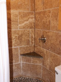 The shower is tiled and has a river rock floor.