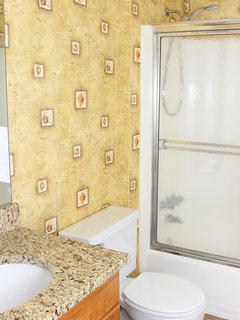 The bath is accessible from the hall. It has a vanity with granite & shower/tub.