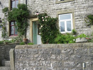 Stone, terrace cottage,roses and honeysuckle round the door.