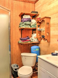 This bathroom features a single vanity, walk-in shower, and a variety of towels.