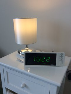 Bedside table including table lamp, clock radio and storage draws.