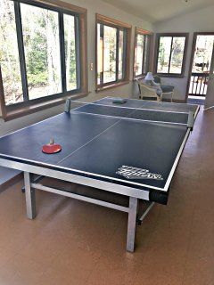 Ping pong table on porch next to kitchen area
