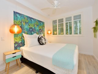 Bedroom with pendant lamps and plantation shutters
