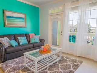 The living room features modern coastal decor and a memory foam queen sleeper sofa