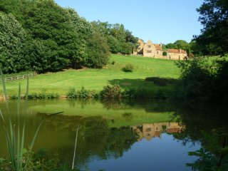 Heath Farm Holiday Cottages reflected in the pond.