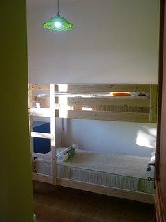 3de slaapkamer met stapelbed en singelbed, uitzicht op achterterras