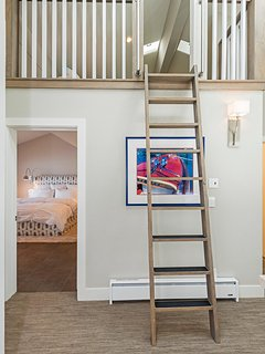 Children's sleeping loft with 3 twin beds is accessible by a ladder.