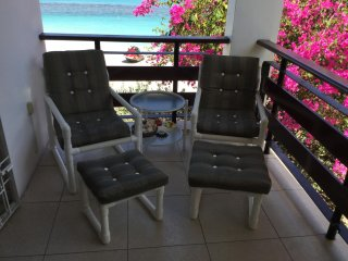 corner of the comfortably furnished balcony overlooking the soft sandy beach bordering the calm sea