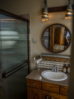 Bathroom features 4x6 walk in shower, wine barrel mirror and light sconces.  Tribute to the ranch!