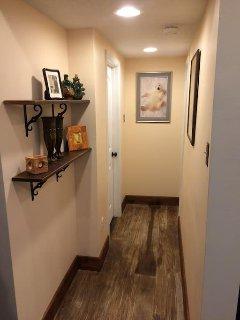 hallway to smaller bedroom and bathroom