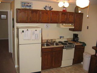 Kitchen area supplied with towels, dishes, utensils, plates, glasses and cook ware