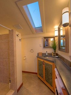 The bathroom has a tiled shower and custom cabinets with a concrete counter top.