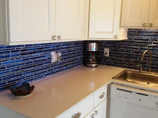 Note the gorgeous new cobalt blue tile, quartz countertops, cabinets with dolphin pulls, dishwasher.