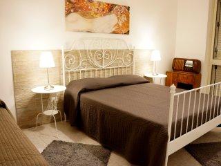 Camera da letto con letto matrimoniale e letto singolo. Stanza abbastanza ampia con finestra.