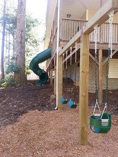 Playground with tube slide and swings of the deck