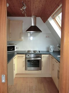 Kitchen with oven/grill, hob, fridge freezer, washing machine, microwave, toaster