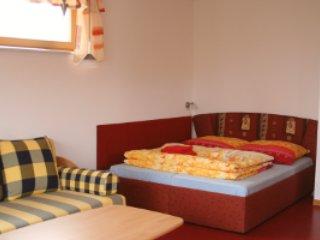 Lit double avec canapé comme lit d'appoint au premier plan