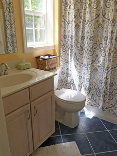 Bright bathroom with tub/shower.