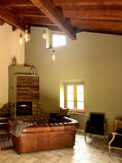 The community room has a wood burning fireplace, leather couch and a vaulted wood beam ceiling.