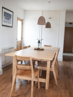 Solid pine table and oak chairs to seat 8 people adjoins lounge/kitchen space.