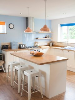 From dining table across breakfast bar into the modern kitchen with dishwasher.