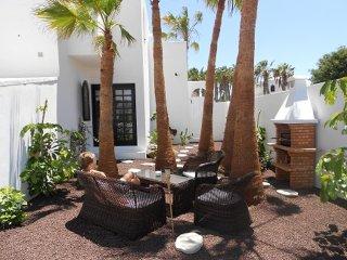 Feriewohnung 'Palm Garden' direkt am Strand mit schönem privaten Garten
