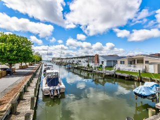 Colorful bayside condo with wraparound, furnished balcony overlooking the canal