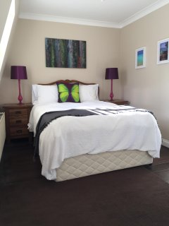 Bedroom with double bed, ensuite with walk in shower with skylight above.
