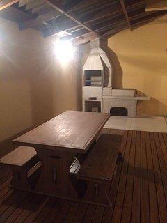 Deck com mesa para 8 pessoas sentadas, e um jogo de 4 cadeiras de jardim e uma rede.