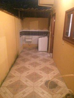 area de serviço com tanque e maquina de lavar e varal.