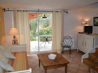 Salon avec lits gigogne, TV, coin cuisine et vue terrasse